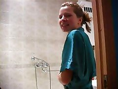 Innocent looking teen in bathrobe having fun in bathroom