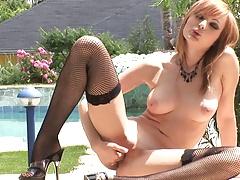 Busty brunette in stockings fucks herself outdoors