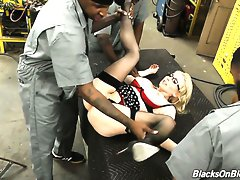 Cute blonde office chick with a bunch of black workers in the factory